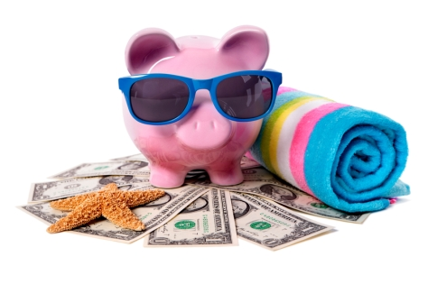 A piggy bank surrounded by money and beach items